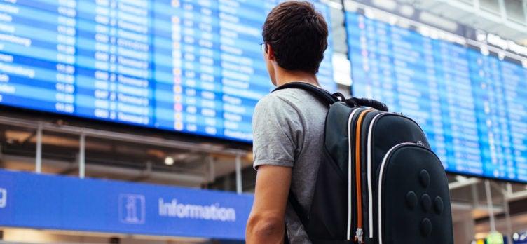 man backpack looking at airport board delay
