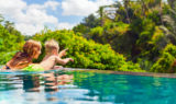 A Guide to Travel for Single Parents - Mom & Son in a Pool