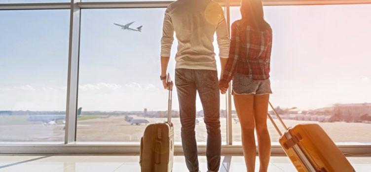 2 passengers look at planes at airport