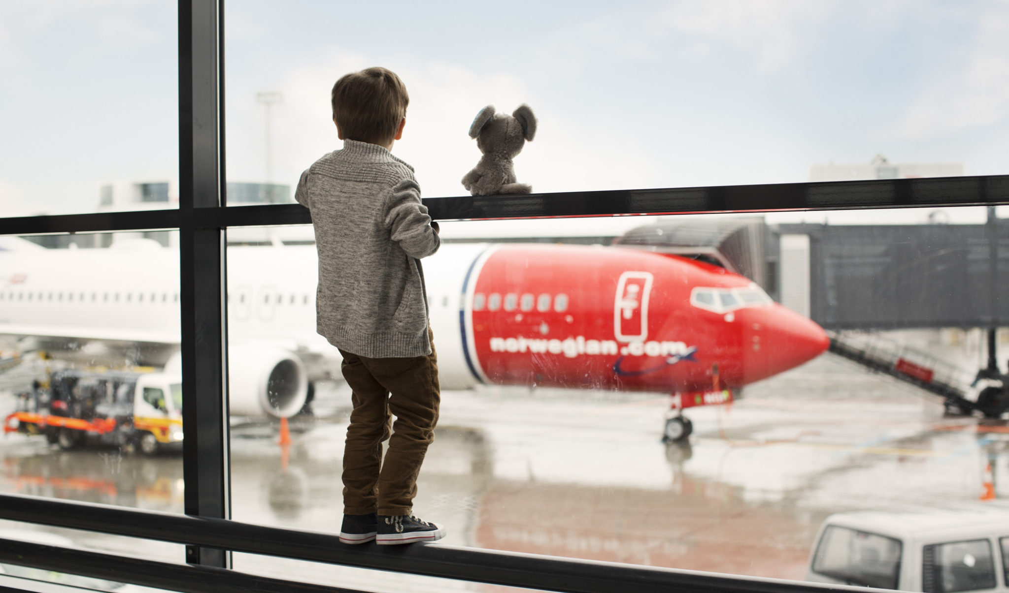 Little Boy Looks Out At Norwegian Plane