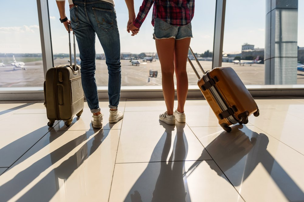 couple in airport with suitcases