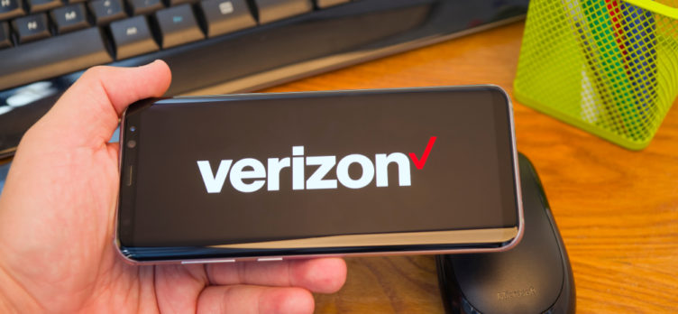 Person Holding A Smartphone Displaying a Verizon Logo