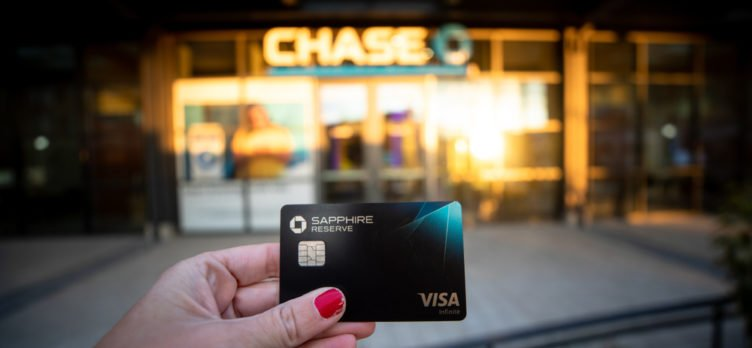 Person Holding Chase Sapphire Reserve Credit Card In Front of A Chase Bank