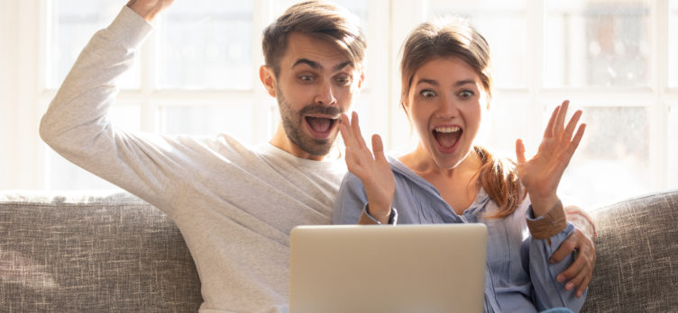 Couple Sititng on Couch Excited with Laptop