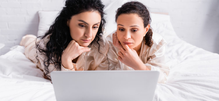 2 women on laptop in thought
