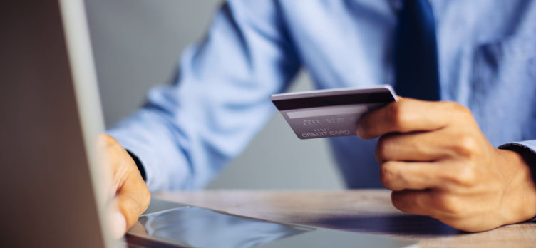 Businessman online payment hands holding credit card and using laptop