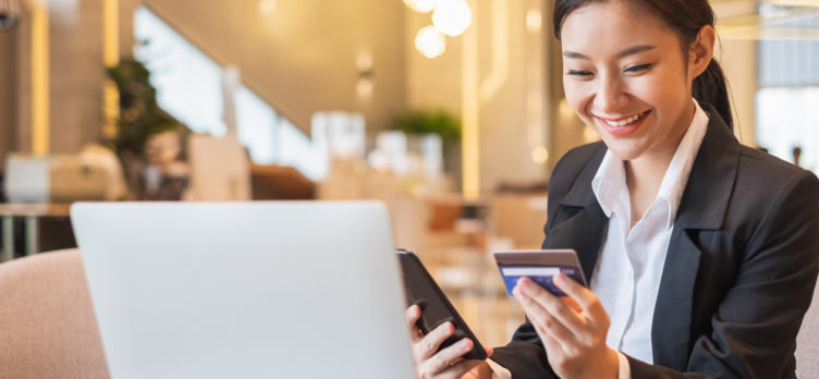 Businesswoman using credit card and mobile phone for online financial payment and shopping