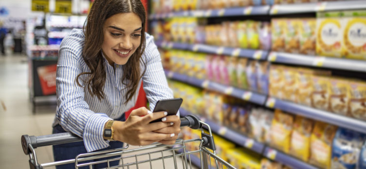 Women on phone leaning on grocery cart in supermarket