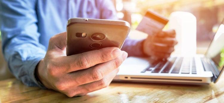 man holding credit card hand entering security code using laptop keyboard online shopping