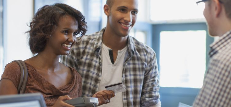 Couple paying at counter with credit card