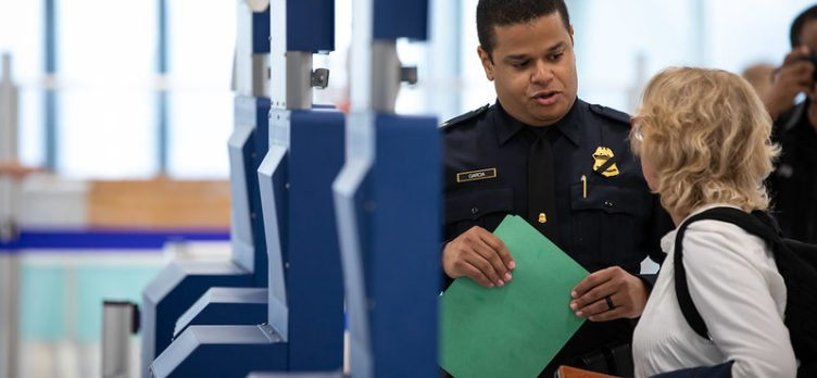 Woman using Global Entry kiosk with CBP agent