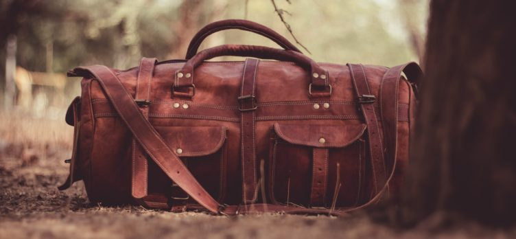leather duffel in woods