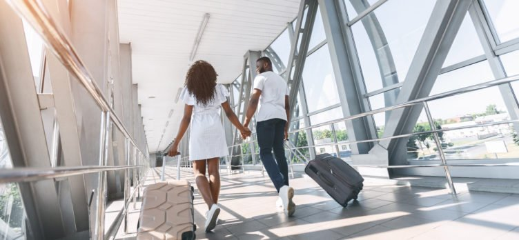 couple walking with bags at airport